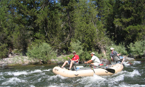 Guide and 2 anglers in tan raft fishing in Blackfoot River whitewater