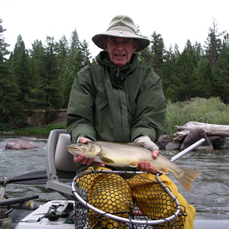 Fisherman sitting in boat holding a Blackfoot River Bull Trout added to testimonials
